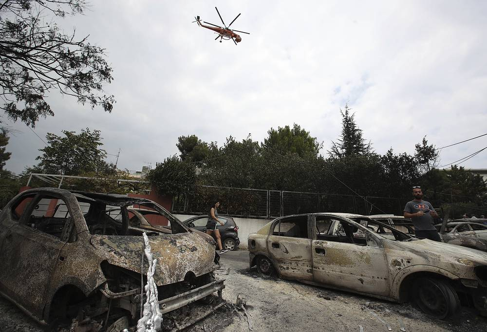 A firefighting helicopter flying above burned-out cars in Mati east of Athens