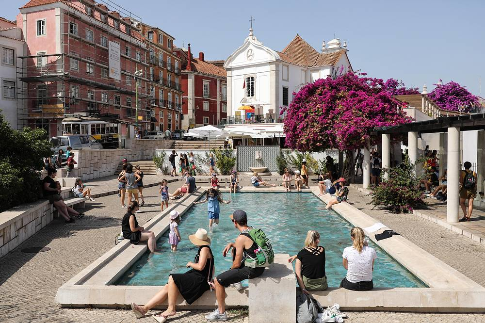 Locals and tourists refresh themselves in a fountain in downtown Lisbon, Portugal