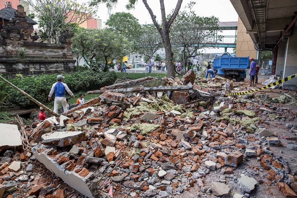 Workers cleanup parts of a shopping mall building which collapsed after an earthquake, in Denpasar, Bali
