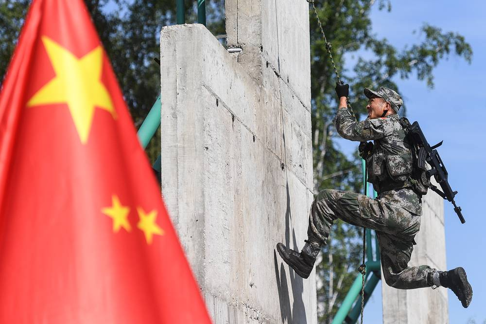 A serviceman of the Chinese People's Liberation Army takes part in the Scout Trail obstacle course