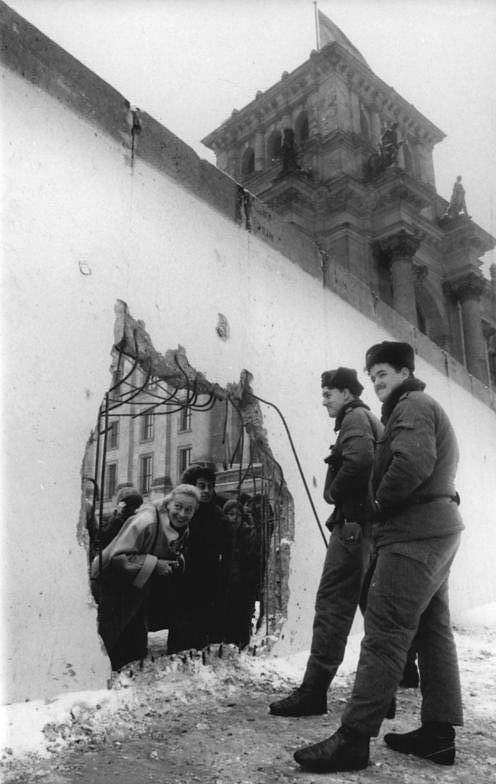 West Germans peer at East German border guards through a hole in the wall, 1990