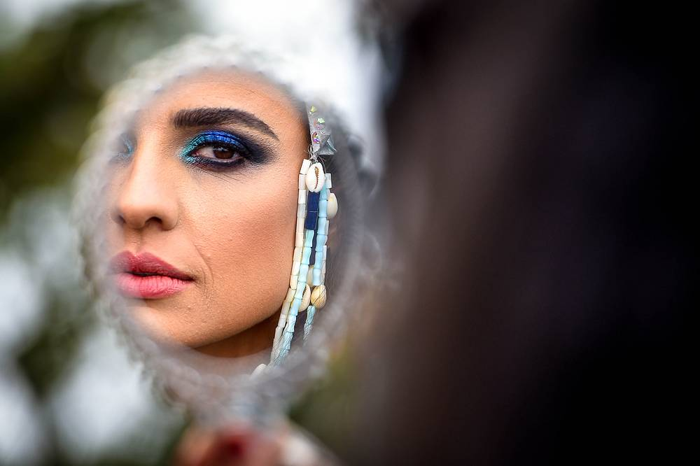 A performer looks in a mirror as she prepares for the Notting Hill Carnival