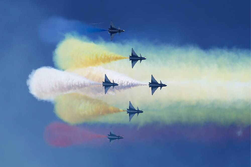 Visitors watch J-10 jet fighters of the Chinese aerobatic team, August 1st (Ba Yi), perform stunts at the Army 2018 International Military and Technical Forum at Kubinka Airfield, Moscow region, August 25