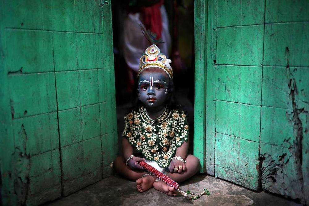 A child sits on a doorstep, dressed as Lord Krishna during Janmashtami festival, which marks the birth anniversary of Lord Krishna in Dhaka, September 2
