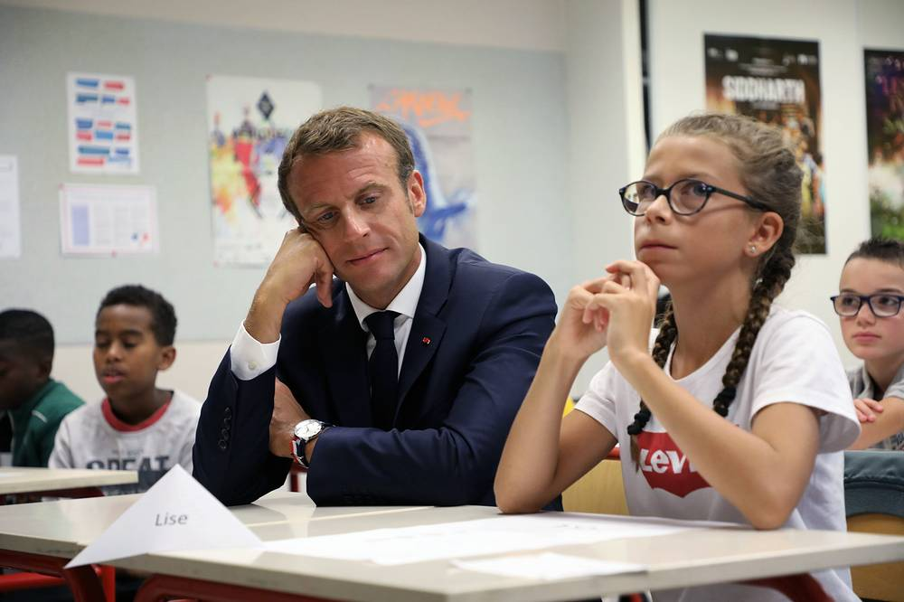French President Emmanuel Macron sits next to a pupil and looks at her worksheet in a classroom during his a visit to a school in Laval, September 3