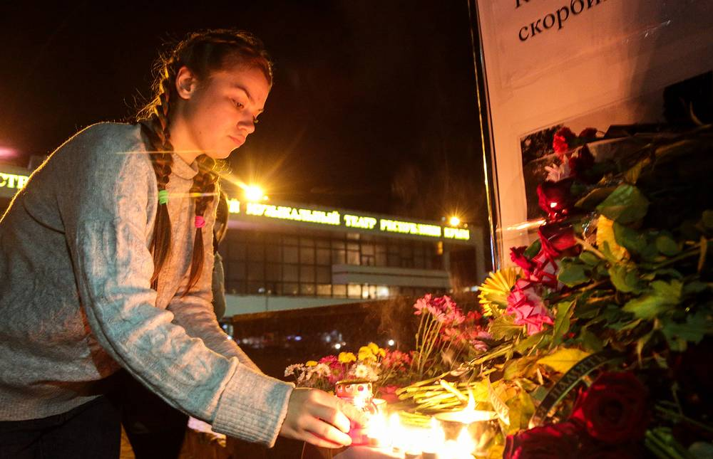 Around 50 people were taken to local hospitals, with ten of them in intensive care units in grave condition. Photo: A young woman lights a candle in the city of Simferopol, Crimea