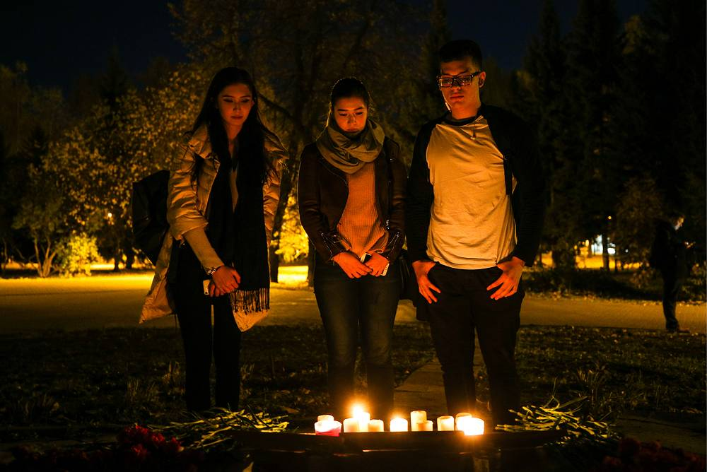 Flowers and lit candles left by mourners in Leninsky Sad Garden in Kazan