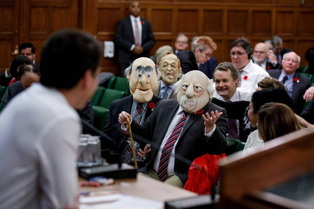 Canadian Prime Minister Justin Trudeau is met by people wearing masks of the Muppets characters Statler and Waldorf during a caucus meeting on Halloween in Ottawa, October 31