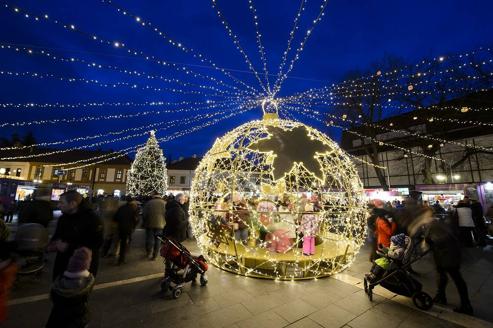 Visitors walk inside a huge, ball-shaped illuminated Christmas decoration set up at Dobo square in Eger, Hungary