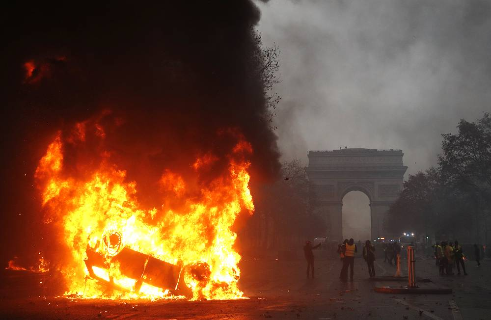 Cars engulfed in flames, as protesters wearing yellow vests clash with riot police near the Arc de Triomphe as part of a demonstration over high fuel prices on the Champs Elysee in Paris, December 1