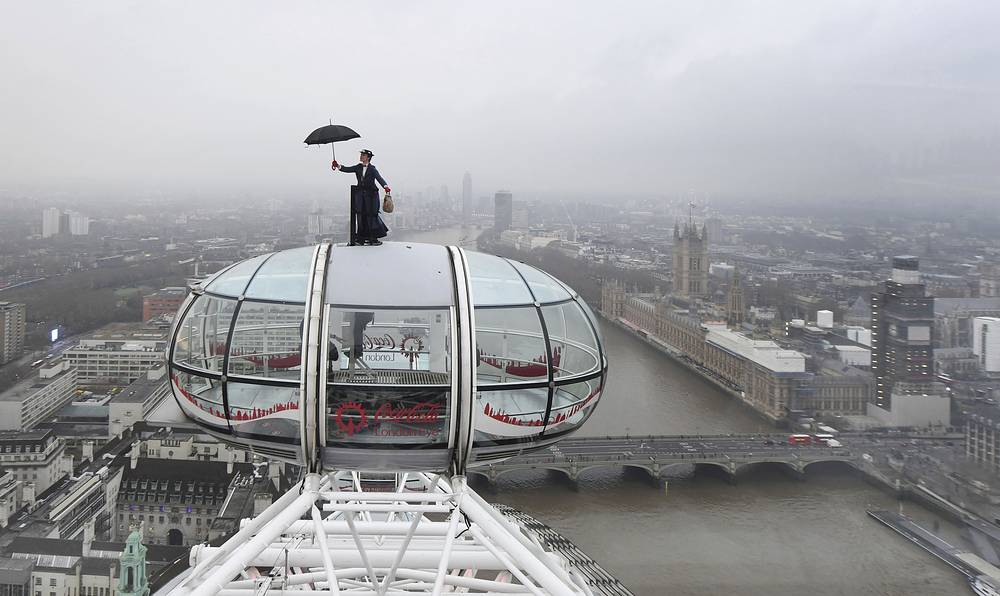 Ahead of the European movie premiere of Mary Poppins Returns, a Mary Poppins stunt double rides atop of the London Eye in central London with the Houses of Parliament on the banks of the River Thames, December 12