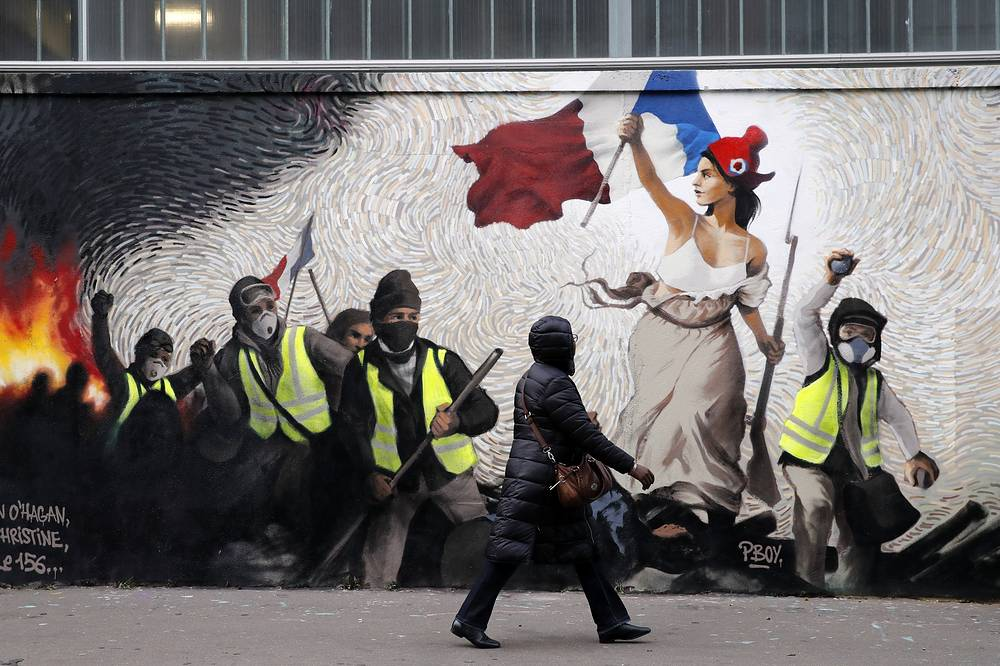 """A woman passes by a mural by street artist PBOY depicting Yellow Vest (gilets jaunes) protestors inspired by a painting by Eugene Delacroix, """"La Liberte guidant le Peuple"""" (Liberty Leading the People), in Paris, January 10"""