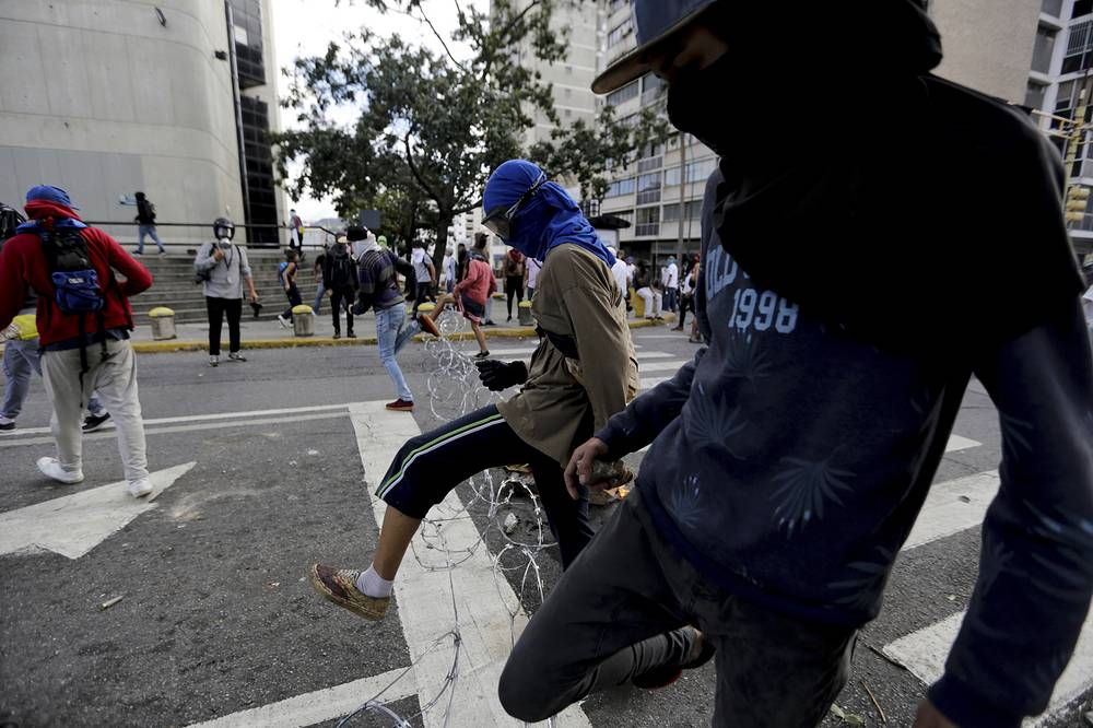 Anti-government protesters jump over a barricade made with wire during clashes with Bolivarian National Guard soldiers after a rally demanding the resignation of President Nicolas Maduro in Caracas