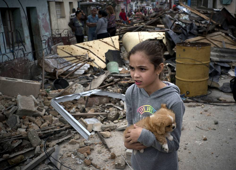 A girl with her dog surveys the destruction left behind by a tornado in Havana
