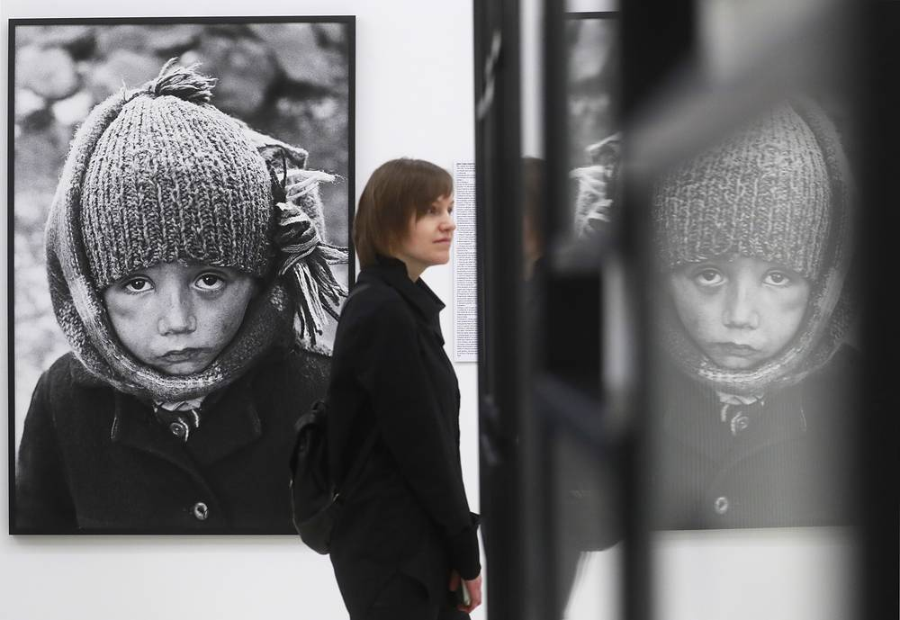 "A visitor views an exhibition of photographs by Yuri Rost, titled ""People"", at the 11th Moscow International Biennale, Fashion and Style in Photography, at Moscow's Manezh Central Exhibition Hall, February 12"
