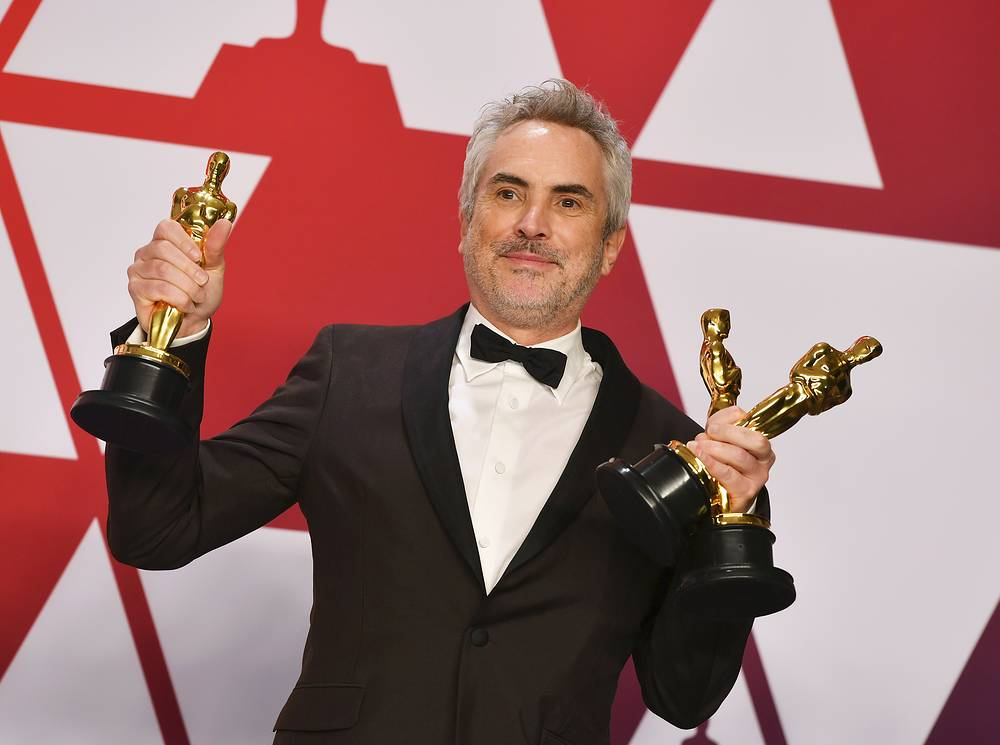 """Alfonso Cuaron poses with the awards for best director for """"Roma"""", best foreign language film for """"Roma"""", and best cinematography for """"Roma"""" in the press room at the Oscars in Los Angeles"""