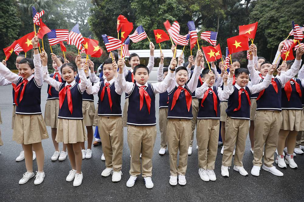 Vietnamese children waving Vietnamese and US flags