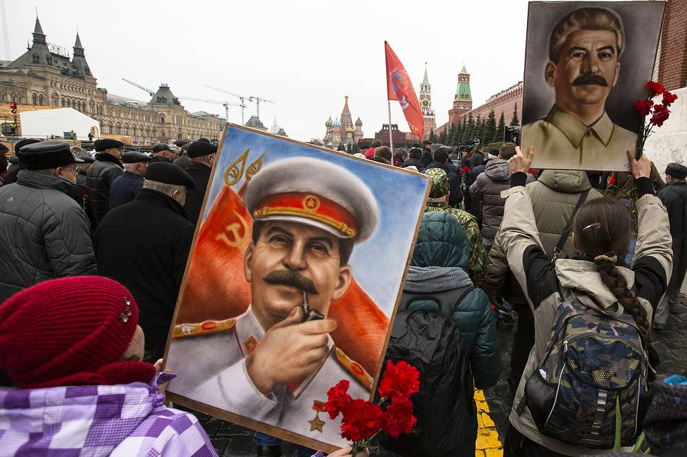 Communist party supporters carry red flags and portraits of Josef Stalin as they walk to place flowers at his grave to mark the 66th anniversary of his death in Red Square in Moscow,  March 5