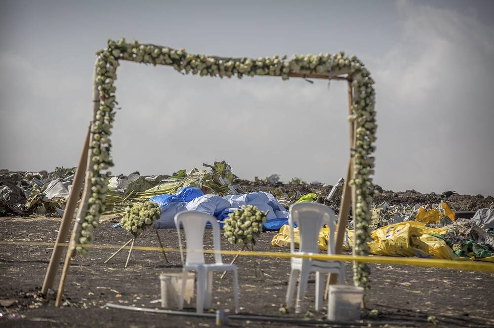 Wreaths and floral installations stand next to piles of wreckage at the scene where the Ethiopian Airlines Boeing 737 Max 8 crashed in Ethiopia