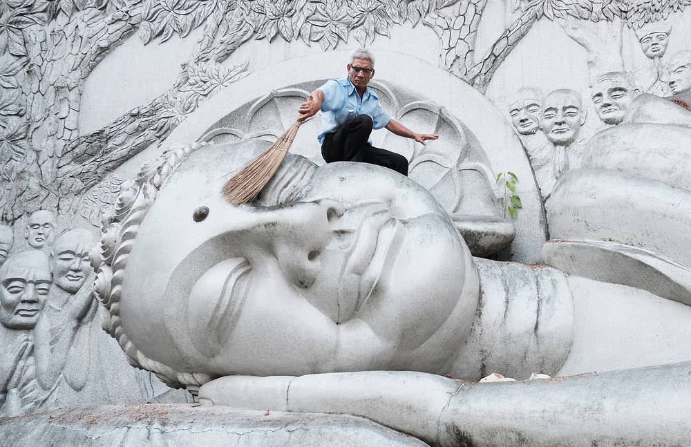 Clearing the fallen leaves from the statue of the Reclining Buddha in the Long Son Pagoda, a Buddhist temple at the foot of the Trai Thuy Mountain in the city of Nha Trang, Vietnam, March 13