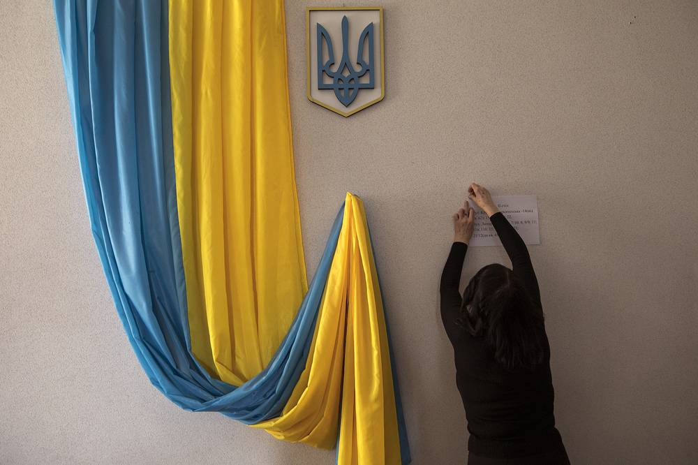 A volunteer makes preparations at a polling station ahead of Sunday's presidential election in Kiev, March 30