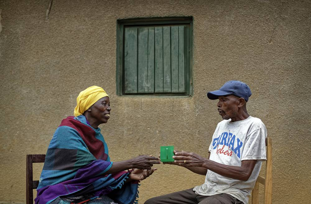 Genocide survivor Laurencia Mukalemera, a Tutsi, is offered a cup of water by Tasian Nkundiye, a Hutu who murdered her husband and spent eight years in prison for the killing and other crimes, are seen at Nkundiye's home in the reconciliation village of Mbyo, Rwanda