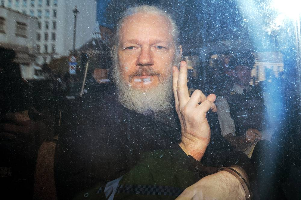 Julian Assange gesturing to the media from a police vehicle on his arrival at Westminster Magistrates court in London, April 11. Wikileaks founder Julian Assange was arrested by Scotland Yard Police Officers inside the Ecuadorian Embassy in Central London. Ecuador's President, Lenin Moreno, withdrew Assange's Asylum after seven years citing repeated violations to international conventions