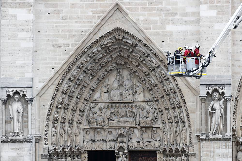 Fire fighters standing in an aerial lift after a massive fire destroyed the roof of the Notre-Dame Cathedral