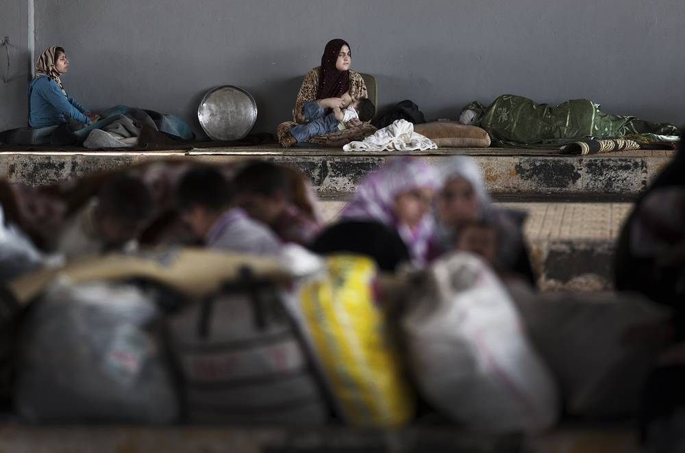 A Syrian refugee mother feeds her child at the Syrian side of Bab Al-Salam crossing border as they wait to cross to one of the refugee camps in Turkey, in the town of Azaz on the outskirts of Aleppo, Syria. AP Photo/ Khalil Hamra