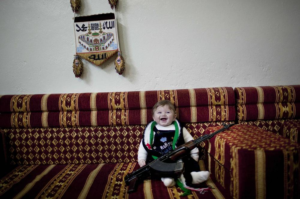 6-months old Maher, laughs as the child is placed to pose with a machine gun placed by supporters of the Free Syrian Army, inside a house near Idlib, Syria, Thursday, Feb. 23., 2012. AP Photo/Rodrigo Abd