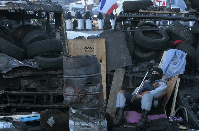 A protester guards the barricade in front of riot police