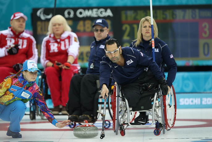 US vice-skip Jimmy Joseph (front) delivers a stone during a Round Robin Session 6 wheelchair curling match against Russia
