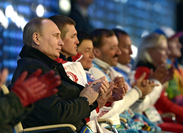 Russian President Vladimir Putin (L) and Roman Petushkov (C), winner of six gold medals at the 2014 Winter Paralympics