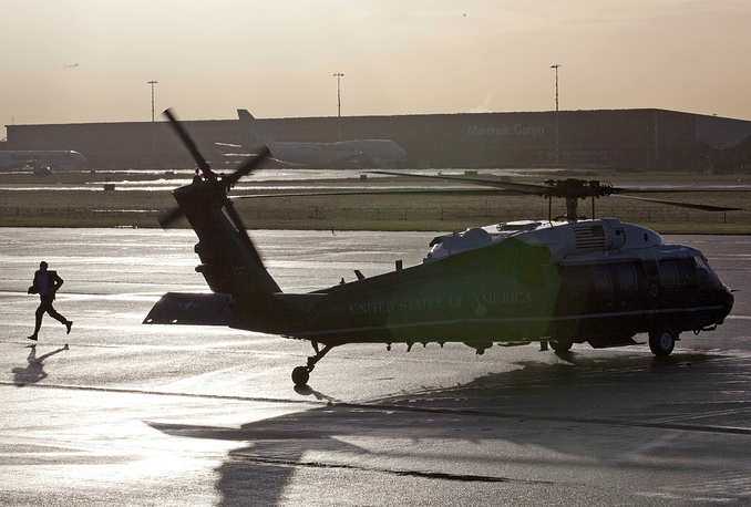 A US secret service agent runs past a United States of America Marine helicopter with US President Barack Obama on board