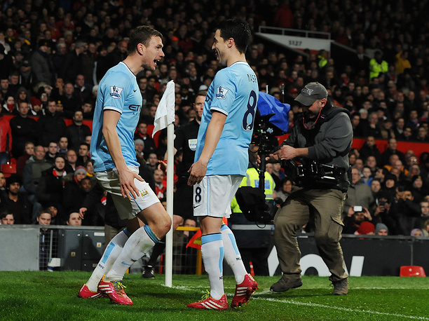 Edin Dzeko (L) celebrates with Samir Nasri scoring the second goal