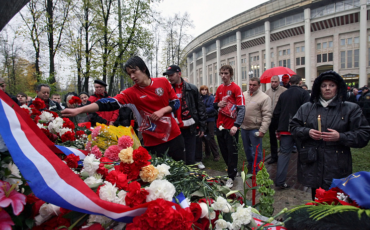 Spectators leaving the stadium at the end of the game rushed back following a late goal, which caused a trampede. Photo: Russian soccer fans and players lay flowers at a memorial to thevictims of the tragedy