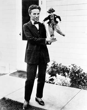 "Charlie Chaplin holding a doll of  ""the Tramp"", 1917"