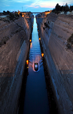 The Corinth Canal connects the Gulf of Corinth with the Saronic Gulf in the Aegean Sea. Photo: a view of Corinth Canal by night as seen from Loutraki