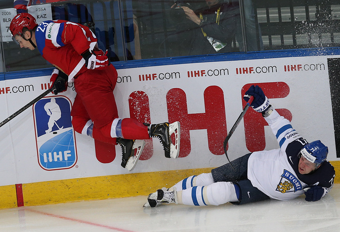 Russia's Dmitry Orlov (L) and Finland's Leonid Komarov fight for the puck