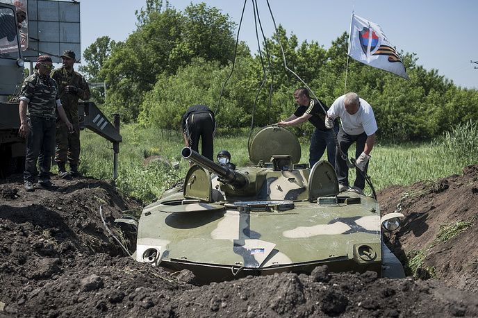 Militia fighters dig in a tank at their checkpoint near Sloviansk