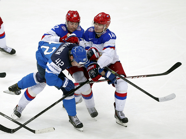 Yevgeni Medvedev (L) and Alexander Kutuzov (R) of Russia in action against Jere Sallinen (C) of Finland