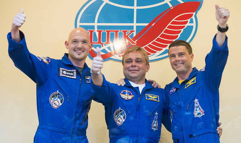 Flight Engineer Alexander Gerst of the ESA (left) Soyuz Commander Maxim Surayev of the Russian Federal Space Agency Roscosmos (center) and Flight Engineer Reid Wiseman of NASA