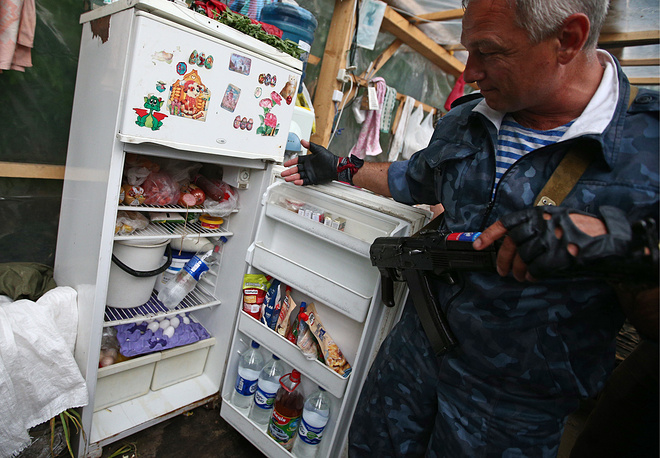 A militia fighter looks in the fridge at a check point