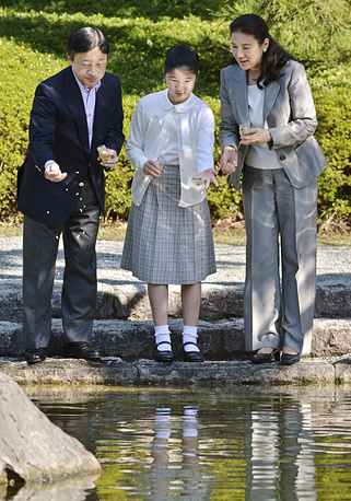 Japanese Crown Prince Naruhito, Crown Princess Masako, and their daughter Princess Aiko feed the carp swimming in a pond during a visit to Shiosai Park in Hayama, Kanagawa prefecture, near Tokyo