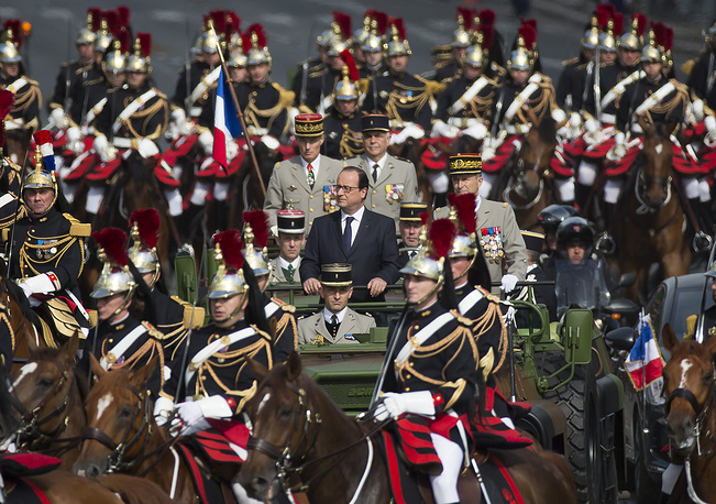 French President Francois Hollande (center) rides atop a command car flanked by members of the Republican Guard