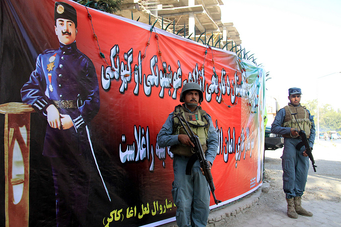 Afghan police officials stand beside the portrait of  Afghan King Ghazi Amanullah Khan during a ceremony to mark the Independence Day in Jalalabad, Afghanistan