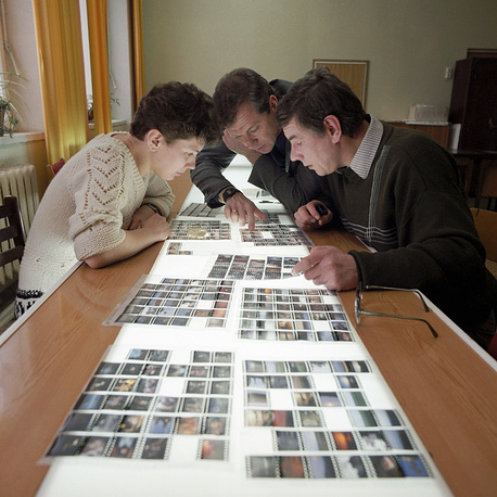 Photoreporters and an editor examine pictures brought by a photographer, 1988