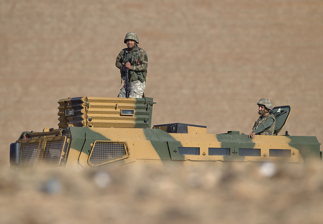 Photo: Turkish soldiers stand on an armored vehicle on a hilltop overlooking the Syrian town of Kobani, Turkey, near the Turkey-Syria border, Oct. 26, 2014