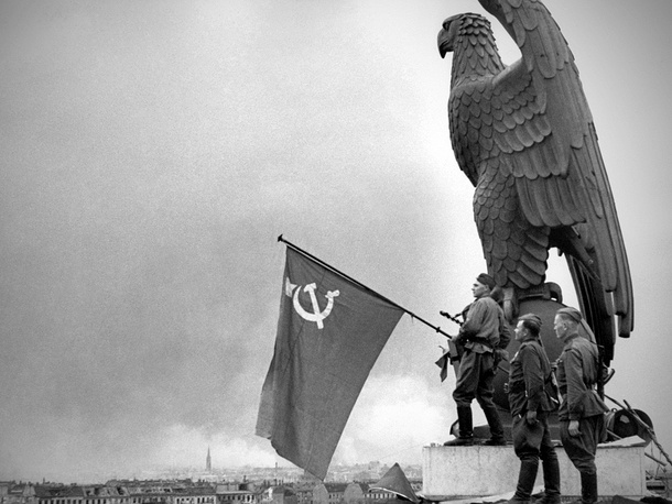 Red Army soldiers hang the Soviet flag over the building of airport in Berlin, 1945