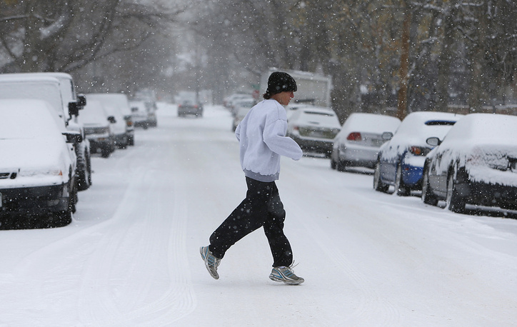 Photo: A jogger in snow-covered street in Denver, November 12, 2014